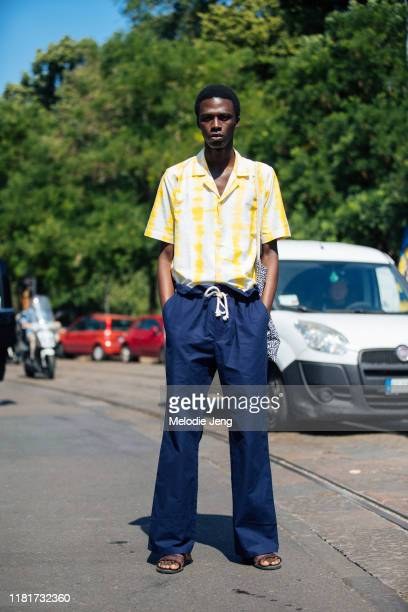 Model Cherif Douamba wears a yellow print top, blue pants, and brown sandals after the Fendi show during the Milan Men's Fashion Week Spring/Summer...