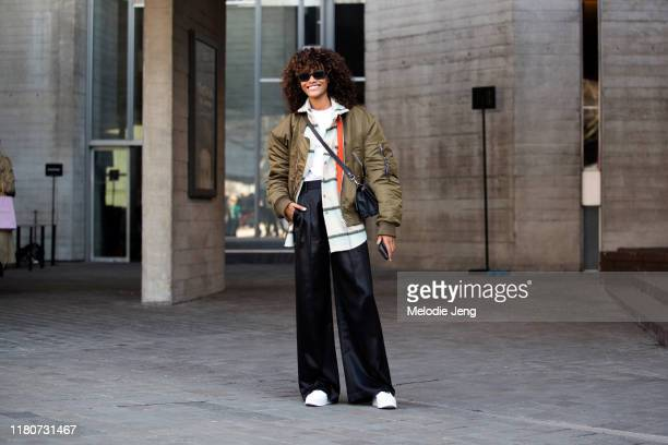 Model Chey Carty wears a green Acne Studios bomber jacket white top and black widelegged trousers after Roland Mouret during London Fashion Week...