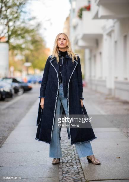 Model Cheyenne Tulsa is seen wearing navy denim coat Blanche flared denim jeans Find Official snake print boots turtleneck on October 24 2018 in...