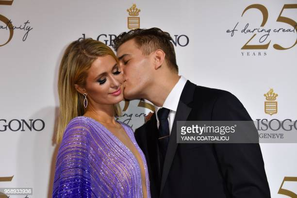 US model Chris Zylka kisses his companion US personality and entrepreneur Paris Hilton during a photocall as they arrive to attend the de Grisogono...