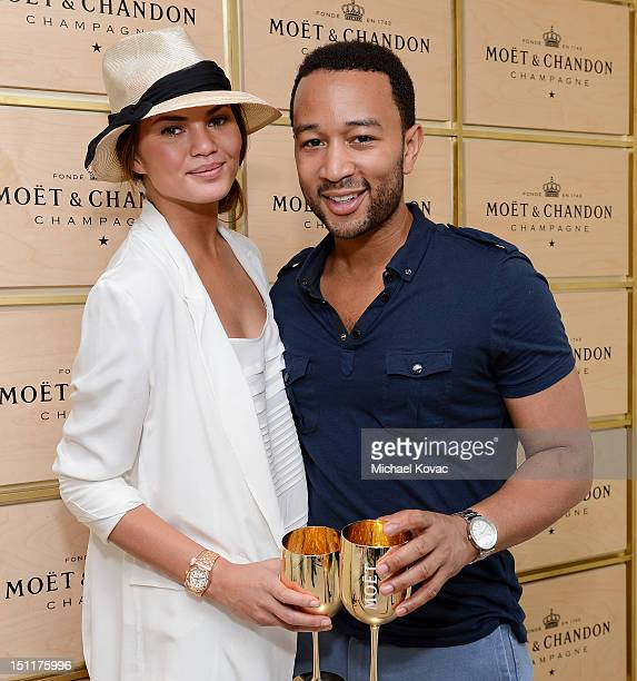 Model Chrissy Teigen and singer John Legend visit the Moet Chandon Suite at the 2012 US Open at the USTA Billie Jean King National Tennis Center on...