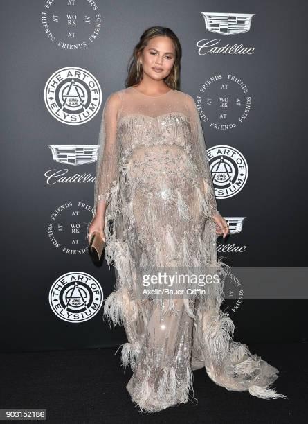 Model Chrissy Teigen arrives at The Art of Elysium's 11th Annual Celebration Heaven at Barker Hangar on January 6 2018 in Santa Monica California