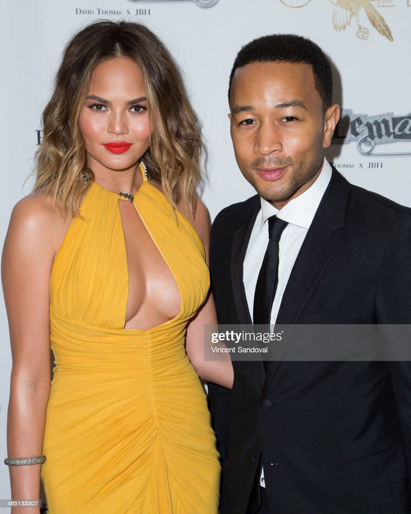 Model Christine Teigen (L) and singer John Legend attend Jason Of Beverly Hills' Pre-GRAMMY cocktail hour and salute to fashion icon David Thomas' Gentleman Collection at The Blvd on January 25, 2014 in Los Angeles, California.