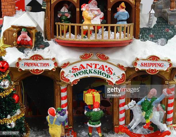 model christmas village with miniature houses, people, winter-scene, santa's workshop - santas workshop stock photos and pictures
