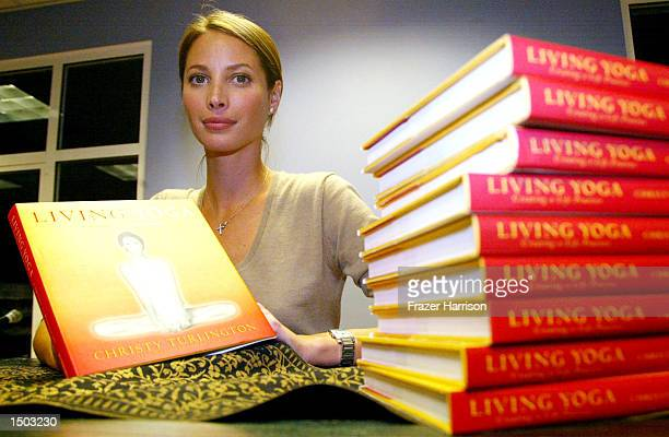 """Model Christy Turlington poses with her new book """"Living Yoga"""" at Borders bookstore on October 17, 2002 in Santa Monica, California."""