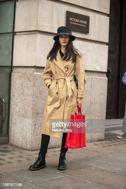 LONDON ENGLAND SEPTEMBER Model Chunjie Liu wears a black bucket hat tan trenchcoat red totebag and black Doc Marten gboots during London Fashion Week...
