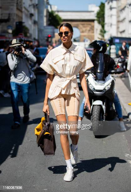 Model Cindy Bruna is seen wearing beige cylce pants knotted button shirt outside Jean Paul Gaultier during Paris Fashion Week Haute Couture...