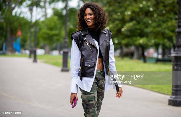 Model Cindy Bruna is seen wearing black leather vest, camouflage pants, white button shirt outside Redemption during Paris Fashion Week - Haute...