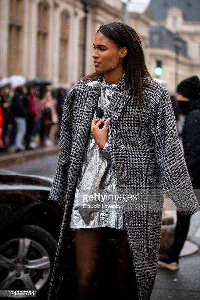 Model Cindy Bruna wearing a checked coat and silver mini dress is seen outside Jean Paul Gaultier show during Paris Fashion Week Haute Couture Spring...