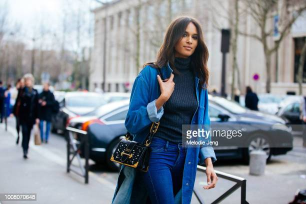 Model Cindy Bruna wears a long denim jacket gray sweatshirt blue jeans and black Prada bag during Paris Fashion Week Fall/Winter 2017 on March 3 2017...