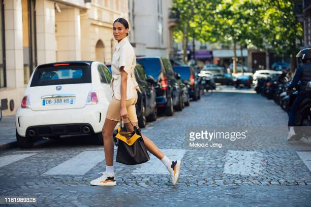 Model Cindy Bruna wears a tan top, tan biker shorts, brown Fendi bag, and Filling Pieces sneakers after the Zuhair Murad show during Couture Fashion...
