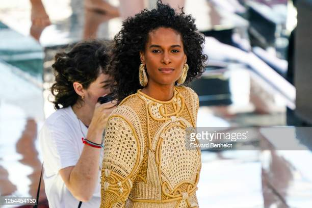 Model Cindy Bruna wears golden large earrings a golden knitted dress with embroidery and geometric patterns during the Balmain Sur Seine Performance...