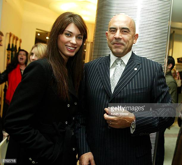 A Model Cinthia Moura and Ferre CEO Enrico Mambelli pose at a party held at Ferre Rodeo Store on November 5 2003 in Beverly Hills California