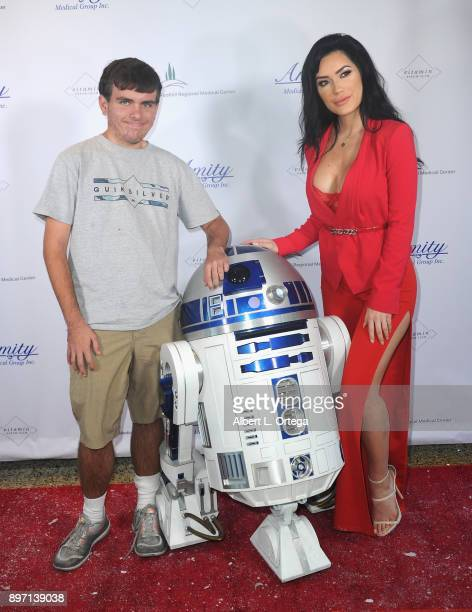 Model CJ Sparxx poses with a patient and R2D2 at A Children's Miracle Holiday Sponsored by Amity Medical Group and Vitamin Patch Club in Partnership...