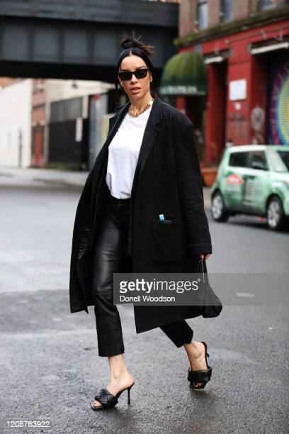 Model Claudia Salinas is seen wearing a white shirt black RTA pants Ann Demumeister black coat Bottega Veneta black heels and black Prada purse...