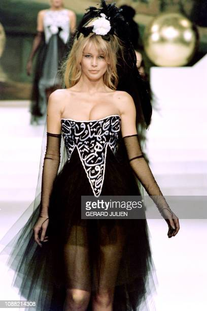 Model Claudia Schiffer presents a dress designed by Karl Lagerfeld with verses from the Koran in a 15 January 1994 photo during the 1994 SpringSummer...