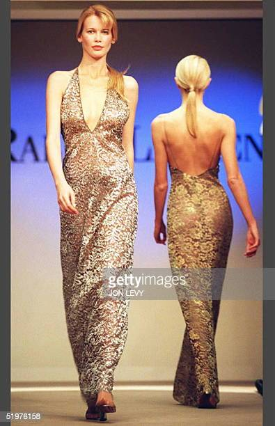 Model Claudia Schiffer wears an embroidered gold lace plunging neck dress during the showing of the Ralph Lauren Fall 1996 fashion collection 03...