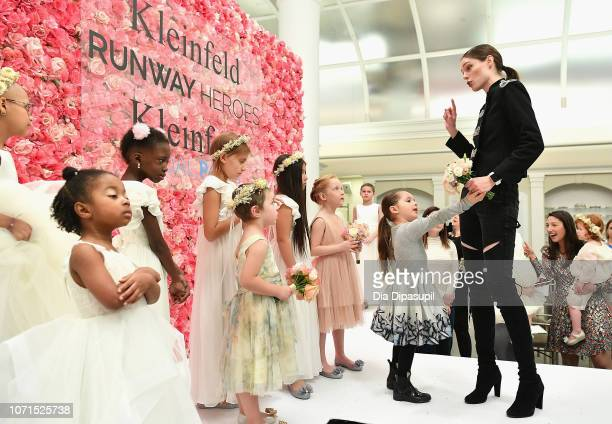 Model Coco Rocha teaches 30 childhood cancer fighters and survivors to walk the runway as her daughter Ioni James Conran looks on during Runway...