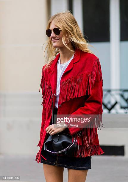 Model Constance Jablonski wearing a black Loewe bag and red jacket with fringes outside Balmain on September 29 2016 in Paris France