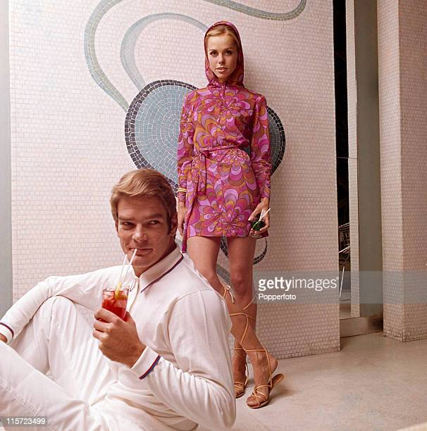 A model couple both with blonde hair he seated sipping a drink through a straw wearing white trousers and a white longsleeved knit shirt trimmed at...
