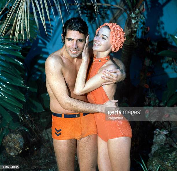 A model couple sheltering from the rain under a palm tree in a studio setting he with his arms around her wearing an orange belted swimsuit and she...