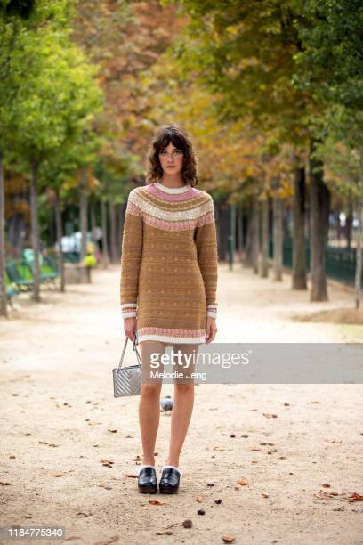 Model Cris Herrmann wears a caramel/pink knit Chanel dress, silver Chanel purse, and black leather clogs wears a after the Chanel show during Paris...