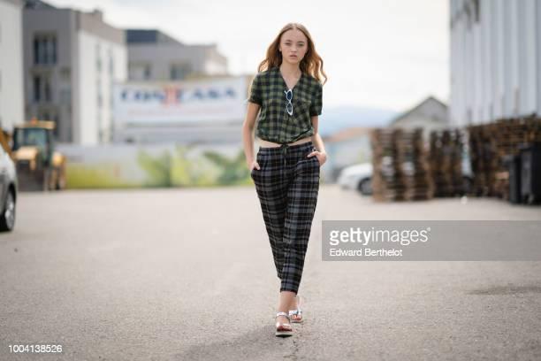 Model Cristina Padure wears a green checked pattern shirt checked print pants sunglasses on July 22 2018 in Sibiu Romania