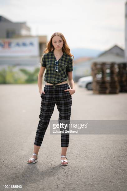 Model Cristina Padure wears a green checked pattern shirt checked print pants sunglasses on July 22 2018 in Sibiu Romania