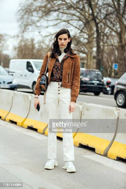 Model Cyrielle Lalande wears a cropped brown suede jacket, red print top, white corduroy button-up pants, and white Balenciaga chunky sneakers after...