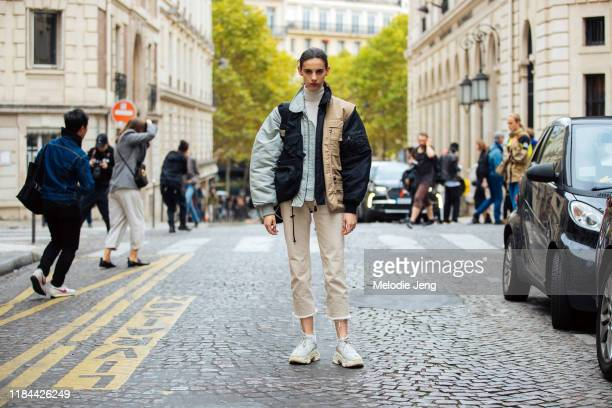 Model Cyrielle Lalande wears a multicolor vision utilitarian bomber jacket with pockets tan cropped pantsand white Balenciaga Triple S sneakers after...