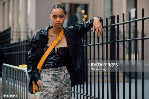 Model Daisy Oh wears a snake earrings, black jacket, black corset top, yellow cross-body bag, and green camouflage pants after the Tory Burch show on...