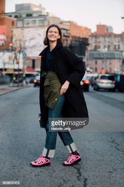 Model Daniela Kocianova wears a black jacket, a sweatshirt around the front of her waist, blue jeans with an exposed hem, and pink Supreme Nike ACG...