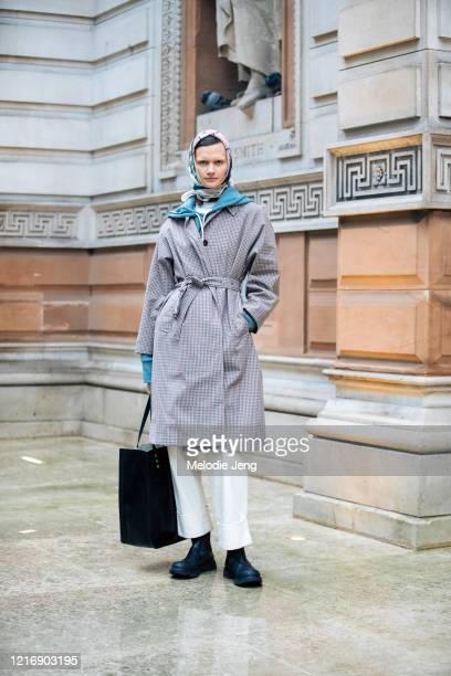 Model Daniela Kocianova wears a print headscarf, Giulia Studios, Sonia Carrasco, a belted light brown gingham coat, black leather shopping bag, white...