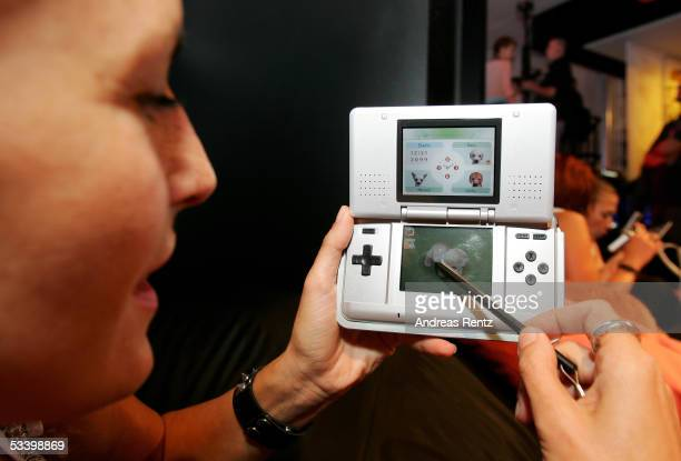 """Model Daniela Schaar plays the game """"Nintendogs"""" on a """"Nintendo DS"""" handheld game station at the Computer Gaming Convention on August 17, 2005 in..."""
