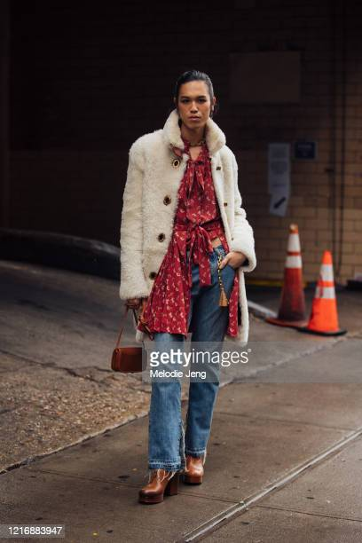 Model Dara Allen wears a white fur jacket, red print top, blue jeans, and brown platform boots. After the Coach show on February 11, 2020 in New York...