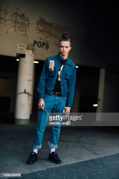 Model Dario Papic wears a denim workwear jacket blue jeans black Fila sneakers and carries a bottle of champaign and a sandwich in his pocket after...