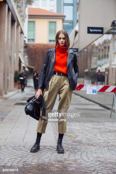 Model Darya Kostenich wears a black leather jacket, a red turtleneck sweater, khaki pants, and black boots during Milan Fashion Week Fall/Winter...