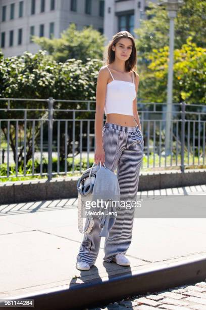 Model Dasha Denisenko wears a white crop top black and white striped pants during New York Fashion Week Spring/Summer 2018 on September 13 2017 in...
