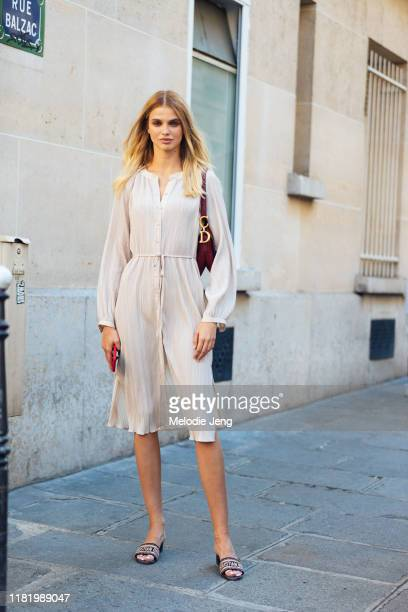 Model Dasha Khlystun wears a Dior bag, cream dress, and Dior sandals after the Zuhair Murad show during Couture Fashion Week Fall/Winter 2019 on July...