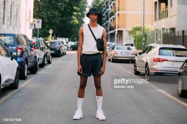 Model David Van Brusselt after the Prada show in a black bucket hat white sleeveless knit top black crossbody bag black gym shorts Nike anklehigh...