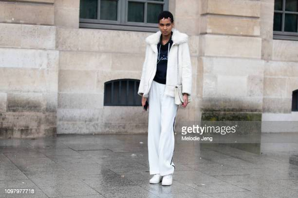 Model Debora Vanoverberghe wears a white shearling coat black shirt black pants and black sneakers after the Alexis Mabille show during Couture...