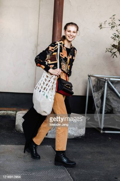 Model Deirdre Firinne wears a tan printed shirt, light brown pants, black boots, a large knit bag, and a black Alexander McQueen Story bag after the...