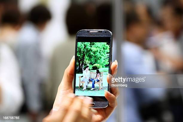 Model demonstrates a Galaxy S4 smartphone manufactured by Samsung Electronics Co. During the unveiling of NTT DoCoMo Inc. New smartphones in Tokyo,...