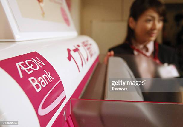 A model demonstrates Aeon Bank Ltd's automated teller machine at a news conference in Tokyo Japan on Thursday Oct 11 2007 Aeon Co the largest...