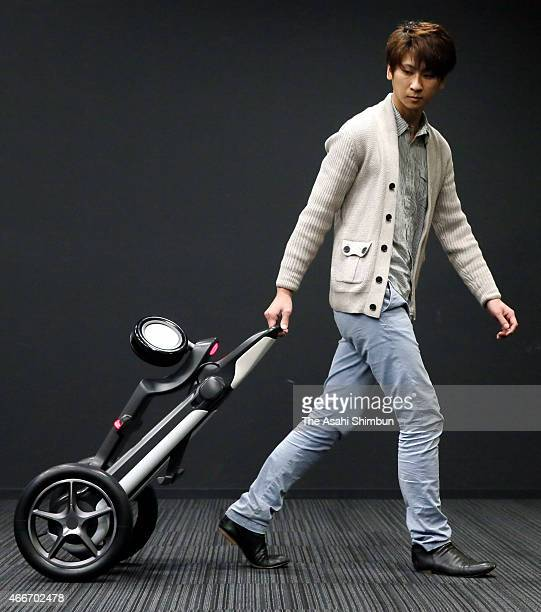 A model demonstrates electronic tricycle 'IlyA' carry mode during its unveiling on March 17 2015 in Tokyo Japan The vehicle's four configurations are...