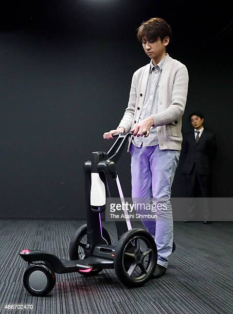 A model demonstrates electronic tricycle 'IlyA' cart mode during its unveiling on March 17 2015 in Tokyo Japan The vehicle's four configurations are...