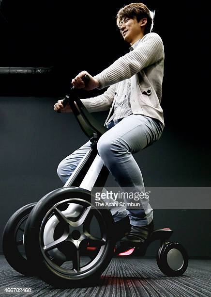 A model demonstrates electronic tricycle 'IlyA' vehicle mode during its unveiling on March 17 2015 in Tokyo Japan The vehicle's four configurations...