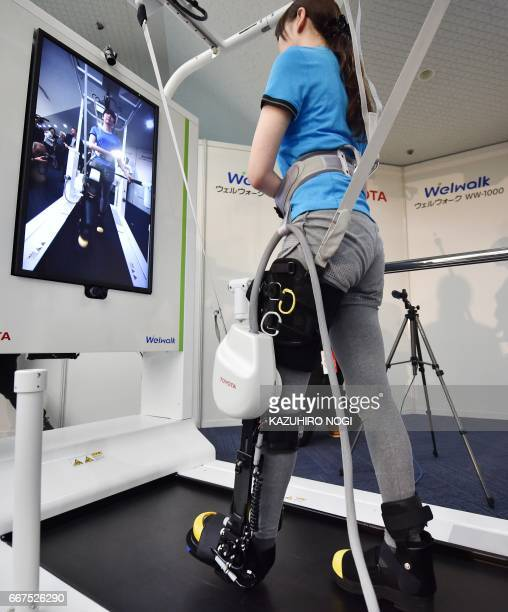 A model demonstrates how the rehabilitationassist robot Welwalk WW1000 developed by Japan's Toyota Motor Corporation helps to assist in flexing and...