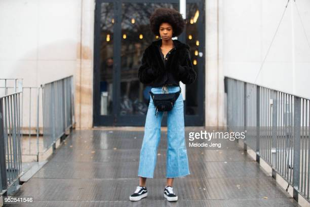 Model Derrionna Rogers wears a cropped black fur jacket a black fanny pack cropped flare jeans and black Vans sneakers on March 04 2018 in Paris...