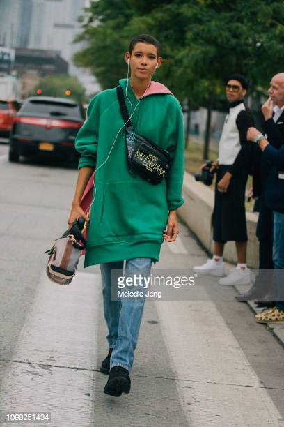 Model Dilone wears a Balenciaga fanny pack oversized green hoodie and Coach bag after the Coach show during New York Fashion Week Spring/Summer 2019...